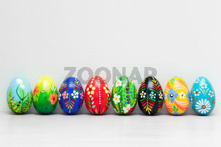 Hand-painted Easter eggs collection on white rustic wall. Floral