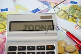 Taschenrechner, Brille und Kugelschreiber auf Euroscheinen