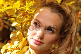Porträt einer jungen Frau vor Herbstlaub