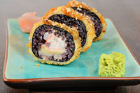 Baked sushi rolls served on blue plate