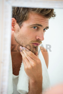 Man checking his stubble in bathroom