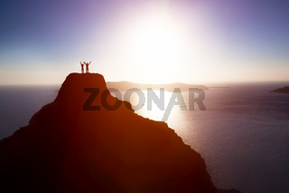 Happy couple on the top of the mountain over ocean celebrating life, success