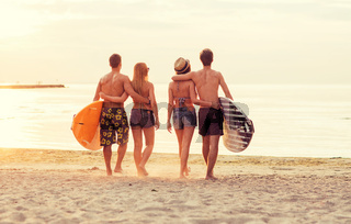 smiling friends in sunglasses with surfs on beach