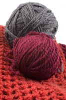 Knits and balls of wool on a white