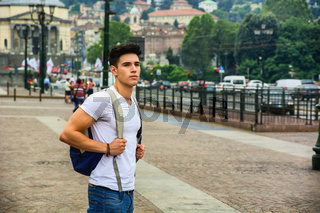 Handsome young man walking in European city square