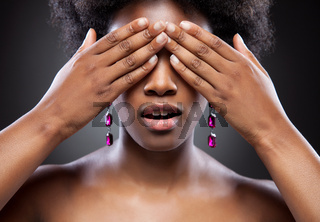 Black beauty covering eyes with both of her hands