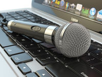 Microphone on the laptop keyboard. Digital audio  music software or karaoke concept.