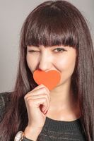 Beautiful funny woman with casual makeup and red heart in hand