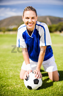 Female football player kneeling on field with ball