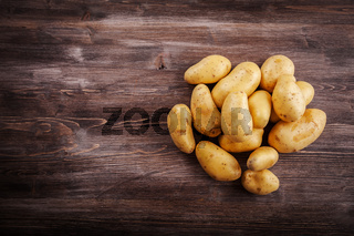 Fresh organic potatoes on a wooden table with copy space