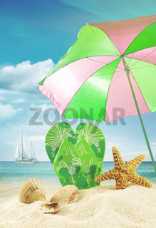 Sandals and seashells with umbrella at the ocean