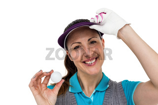 Golf player posing with golf ball
