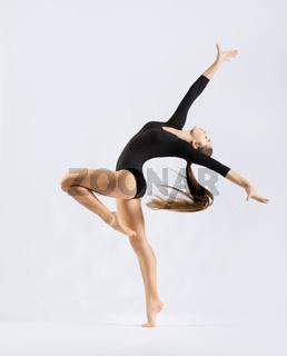 Young girl engaged art gymnastic on grey