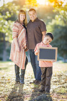 Mixed Race Couple Stands Behind Son with Blank Chalk Board