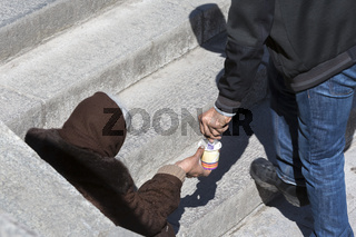 Homeless beggar giving money