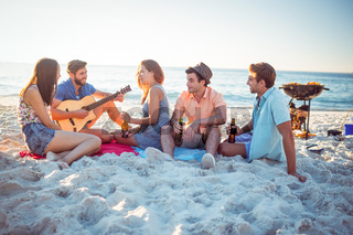 Happy hipsters relaxing and playing guitar