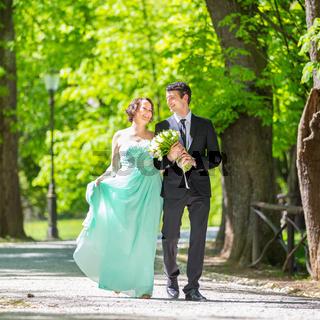 Wedding couple walking in park.