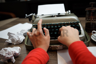 woman typing on old typewriter