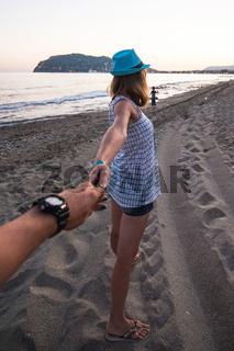Girl holding a hand man on the beach