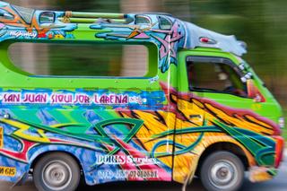 FIlipino Man Driving a Very Colorful Jeepney mini van
