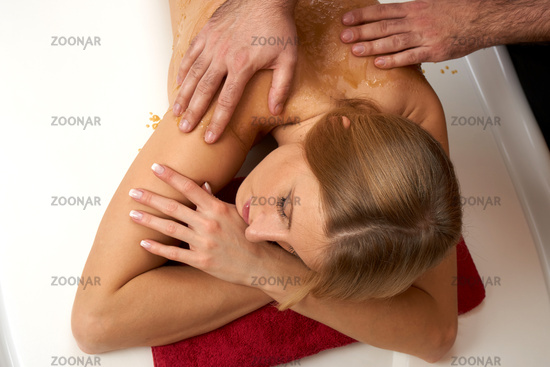 Young woman receiving an honey-salt-massage