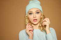 Gorgeous young woman with blond ringlets in a green knitted winter outfit ,over light brown