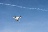 A Quadrocopter with under specified camera flying against a cloudless sky.