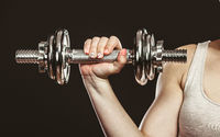 Closeup arm strong woman lifting dumbbells weights