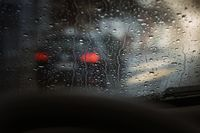 View through wet windshield of a car on the flow of traffic.