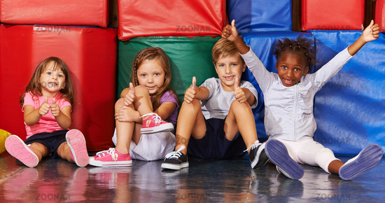 Gruppe Kinder in Turnhalle hält Daumen hoch