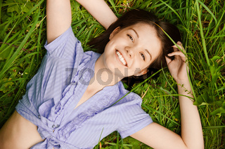 portrait of young brunette woman lying on grass at summer green park