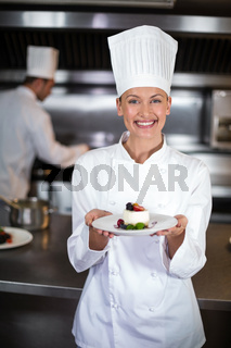 Portrait of smiling female chef holding plate in kitchen