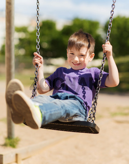 happy little boy swinging on swing at playground