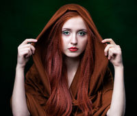 Young woman with ginger hair and scarf on green background