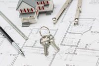 Home, Pencil, Ruler, Compass and Key Resting on House Plans