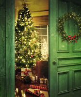 Rustic door opening into a room with Christmas tre
