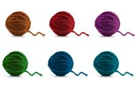 Multi-colored balls of wool on a white