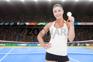 Composite image of female athlete holding medal