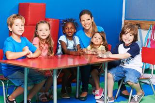 Children sitting with nursery teacher at table