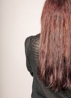 Rear view of a young woman with long brown hair against gray background copyspace