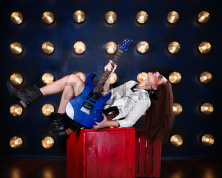 Attractive punk girl with cool make up holding guitar