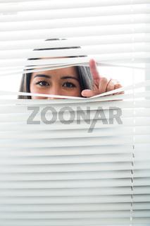 Woman peeking through some window blinds