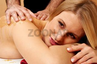 Junge Frau bekommt eine Honig-Alpensalz-Massage