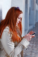 Fashionable Young Woman in Gray Coat Busy with her Mobile Phone Leaning Back Wall in a City