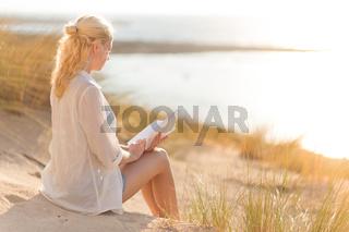 Woman enjoys reading on beautiful sandy beach.