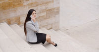 Cute business woman sitting on steps with phone