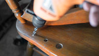 Drilling. Repairing of old chair. Selective focus on drill, shallow dof.