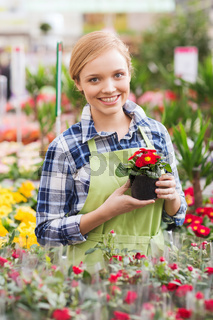 happy woman holding flowers in greenhouse