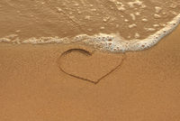 Heart drawing in the sand on the morning beach