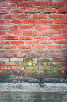 Old red brick wall vertical texture with part of concrete basement beneath